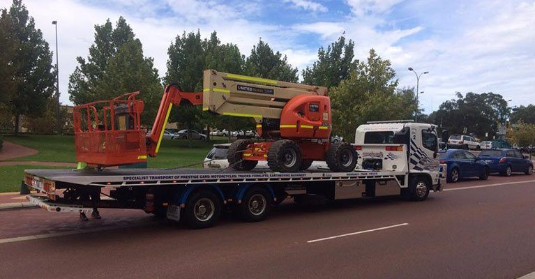 Allout's white tow truck towing red lifting euipment on the street
