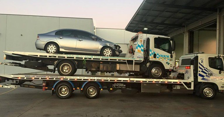 A silver car shown being towed and recovered after an accident