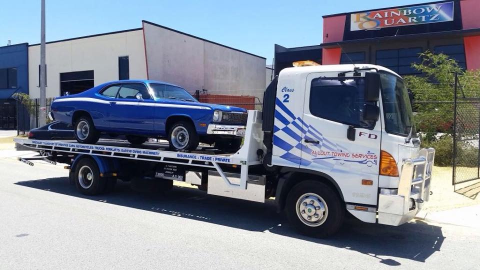 The tilt tray two truck in action, towing a blue car