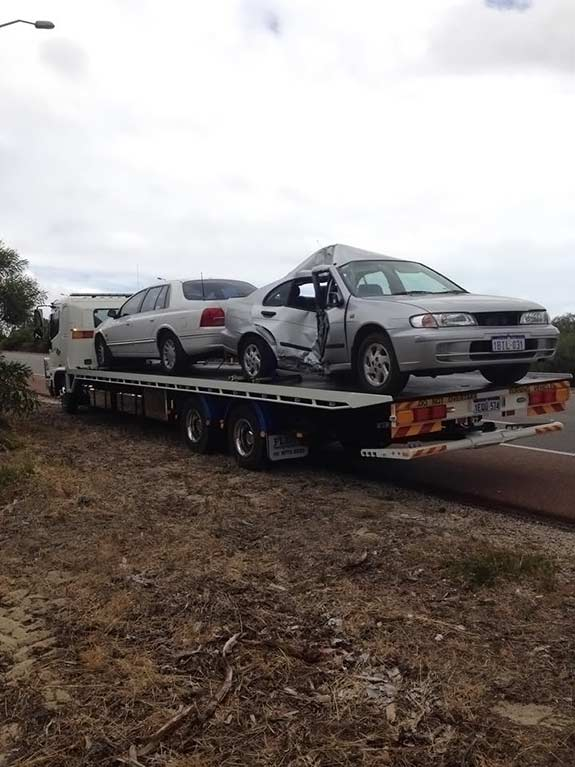 Two crashed cars, one silver and the other white, being towed on Allout's tow truck