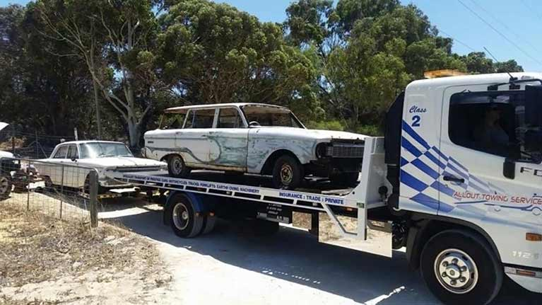 An old white damaged car being towed by Allout's towing service