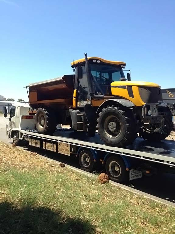 Yellow and dark brown farm truck being towed by Allout's White towing truck