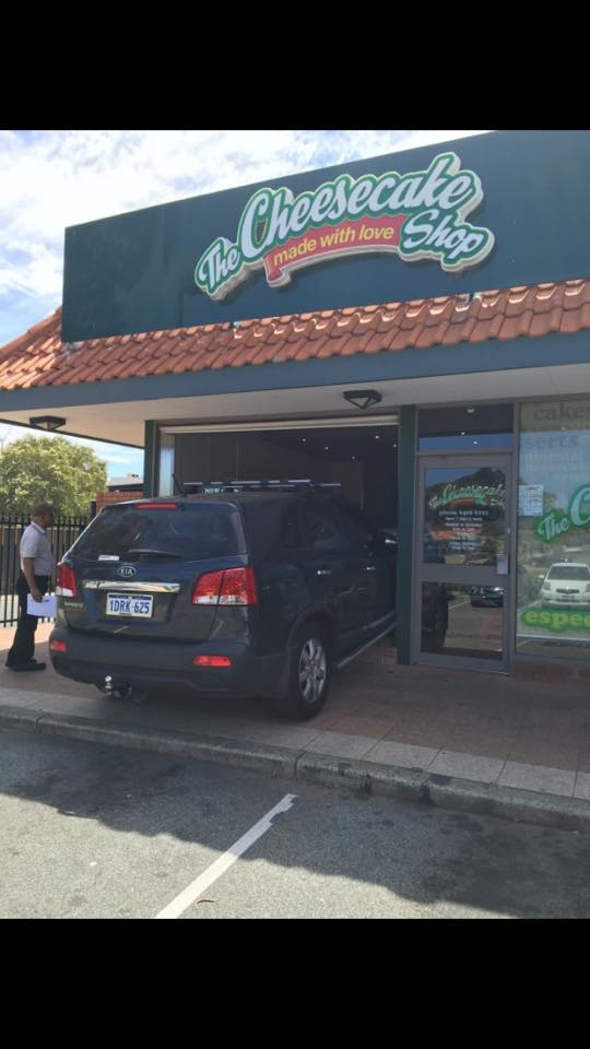 A Kia car shown crashed into a cheese cake shop