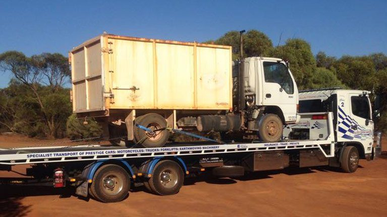 Truck towing another white truck denoting that Allout is prepared to tackle towing job of any size
