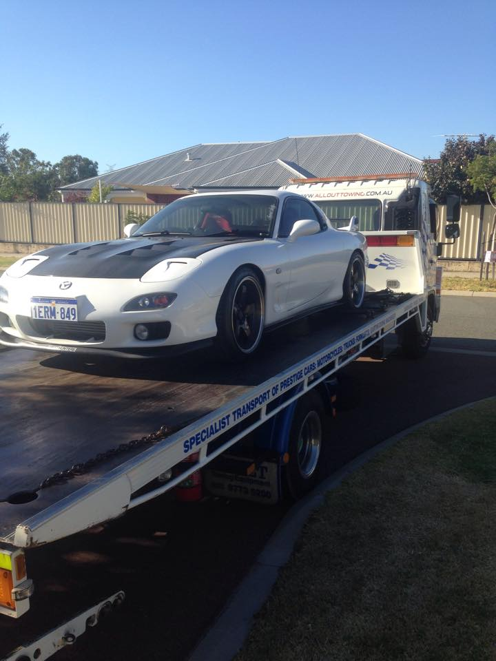 Front view of a white Mazda being towed by Allout's towing truck