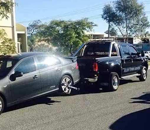 A black sedan with lightly tinted glasses and silver rims towed by Allout's black towing car