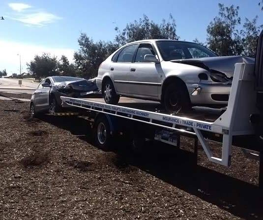 A silver car damaged in an accident being transported by Allout's white towing truck