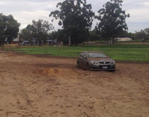 Front view of a holden car stuck in mud with grass and trees in the background