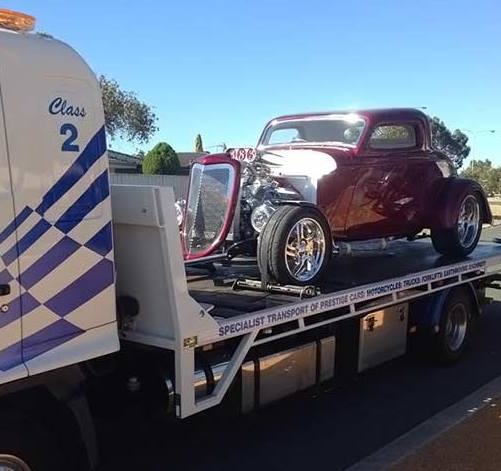 Side view of a white truck numbered 'Class 2' towing a maroon vintage hotrod car