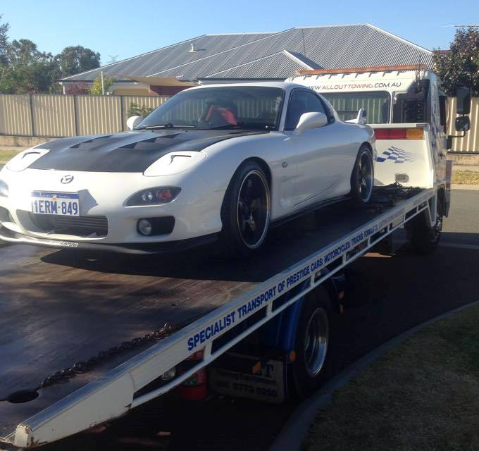 Front angled view of a white mazda car with black hood towed by a white truck